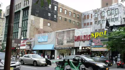 panning across 125th street in Harlem to famous Apollo Theater marquee and entrance sign in NYC