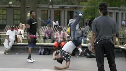 kid breakdancing - spinning on hand in Washington Square Park on summer day - slow motion