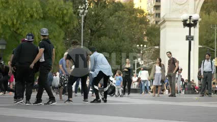 breakdancer doing windmills in circle of hip hop dancers in summer in Washington Square Park in NYC