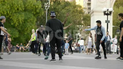 kid flipping and spinning in air breakdancing in Washington Square Park in summer - hip hop dance crew - group dancing