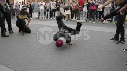 B-boy breakdancing in Washington Square Park on summer day - windmills and spinning in NYC