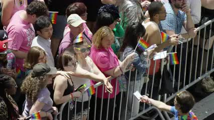 gay pride day - LGBT parade barricade with people waving rainbow flags in NYC