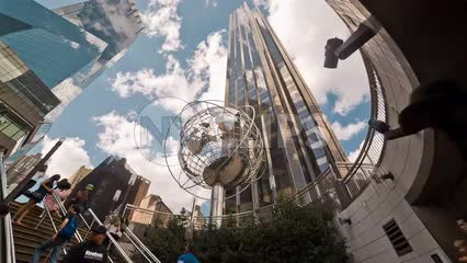 upward view of Trump Tower and steel globe sculpture at Columbus Circle subway station in Midtown Manhattan on summer day - beautiful sky and clouds in NYC