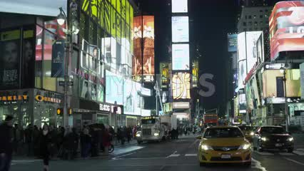 taxi cab driving through Times Square at night with bright lights and billboards in NYC
