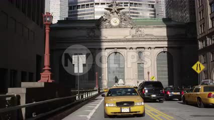 taxi cab driving from Grand Central Station Terminal exterior with clock on Park Ave Midtown Manhattan NYC