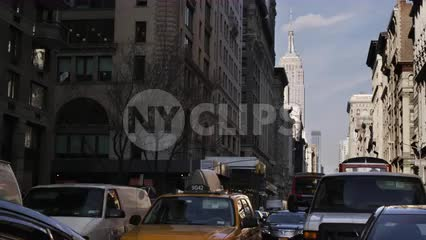 cars stuck in gridlocked traffic on 5th Avenue with Empire State Building in background on Manhattan day
