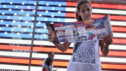 pretty tourist looking at map in front of Times Square American flag LED - slow motion 4K in New York City