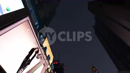 upward angle of animated digital billboards driving through Times Square at night
