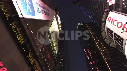 upward angle of tall buildings driving through Times Square at night with bright lights and ticker in NYC