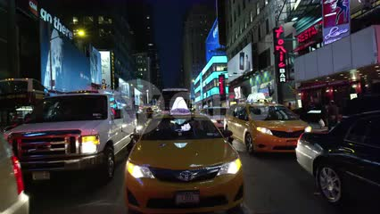 taxi cab driving through Times Square at night in slow motion in NYC