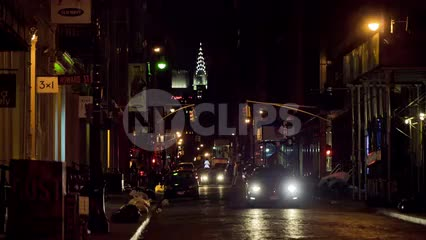 SoHo street at night with Chrysler Building lights in background in NYC
