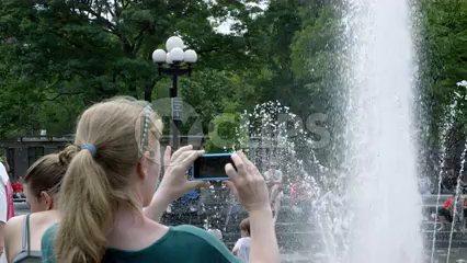 woman taking picture with smartphone of children in Washington Square Park circle fountain in slow motion in summer - 4K NYC