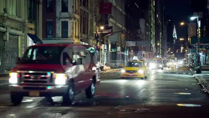 taxi cabs driving in traffic down Broadway in SoHo at night with Chrysler Building in background in NYC