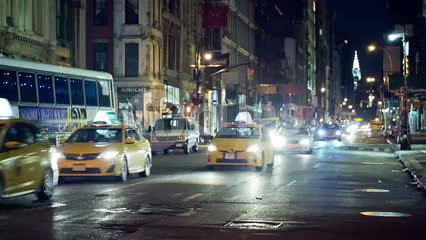 taxicabs driving down Broadway at night with Chrysler Building in background in NYC
