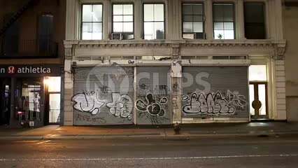 graffiti on store gate at night with cars and taxi cabs driving by in NYC - with audio
