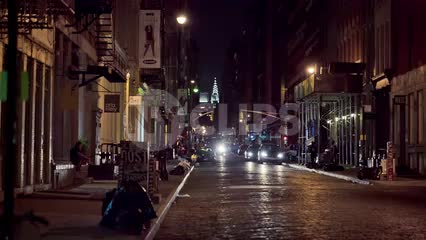 quiet cobblestone street in SoHo at night with Chrysler Building in background - two people crossing