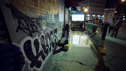 graffiti on wall outside subway station in Lower Manhattan at night