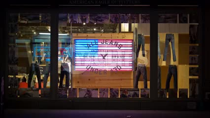 clothing store with rotating jeans display and  American flag LED sign at night on Broadway in NYC