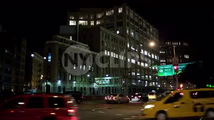 taxicabs at night driving on 7th Ave Varick Street downtown at busy intersection before Holland Tunnel