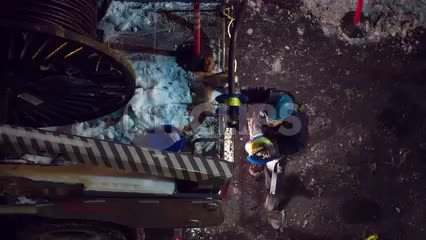 construction workers with hardhats and fiber optic cable spool at night - overhead view of NYC street in winter