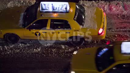 taxi cab driving off in snow storm on slush in street - winter night overhead view in NYC
