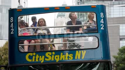 tourists on City Sights bus driving away in Midtown Manhattan NYC
