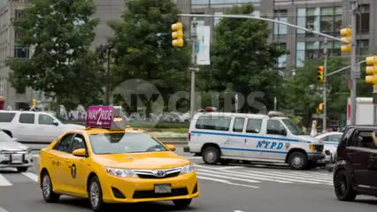 taxi cab driving by Columbus Circle on bright summer day in Manhattan NYC