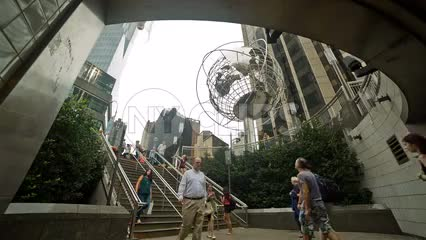 people entering and exiting Columbus Circle subway station stairs with Steel Globe Sculpture overhead on summer day in NYC