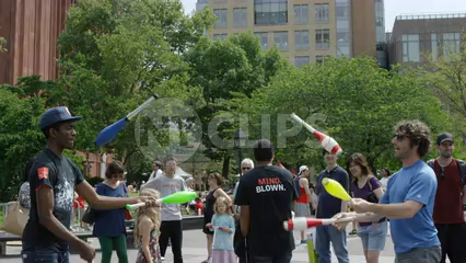 jugglers juggling bowling pins in summertime in Washington Square Park before a crowd in slow motion - 4K NYC
