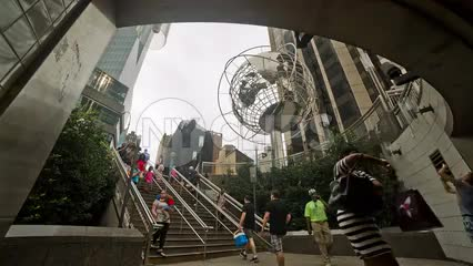Columbus Circle subway station with Steel Globe sculpture and people walking down stairs on summer day in NYC
