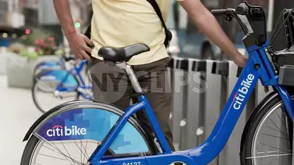 man renting Citi Bike on summer day - close-up on parked blue bicycle in NYC