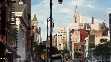Empire State Building and Jefferson Market Library clock tower view from Greenwich Village on summer day in NYC