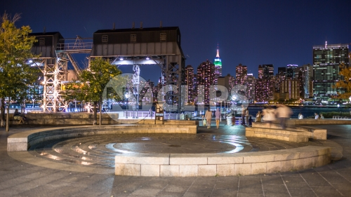 Manhattan skyline at night view from Long Island City circle stone benches and fountain in LIC