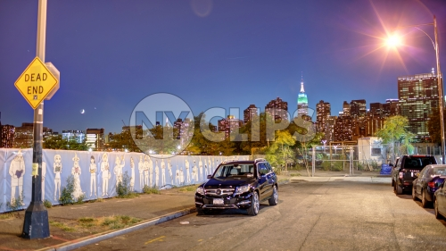 dead end sign in Brooklyn with Empire State Building and skyline in background at night in NYC