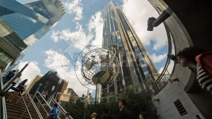 people exiting Columbus Circle subway station by stairs with globe sculpture and Trump Tower overhead on summer day in NYC