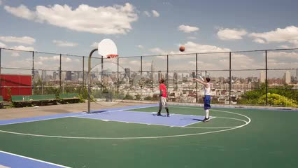 kid shooting and scoring free throw shot in game of 1 on 1 basketball with view of Manhattan skyline through fence on summer day