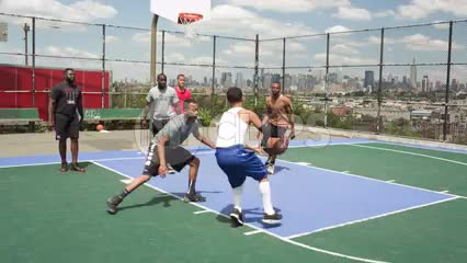 kid makes jump-shot on basketball court in New Jersey with view of Manhattan skyline in NYC on hot summer day