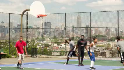kid shooting and scoring jump shot playing basketball on court overlooking Manhattan skyline in NYC with Empire State Building on summer day