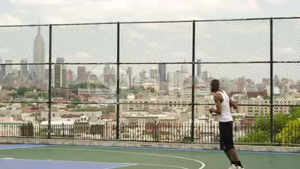 slam dunk - man slamming basketball with both hands off backboard - dunking with Empire State Building view through fence on summer day