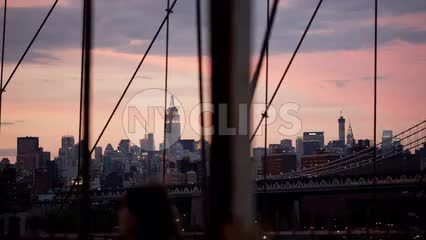 Empire State Building and Manhattan skyline - beautiful sunset view from Brooklyn Bridge in early evening in NYC