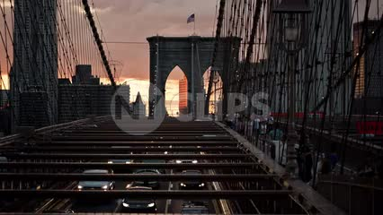 cars driving in slow traffic on Brooklyn Bridge with American flag at sunset in early evening in NYC