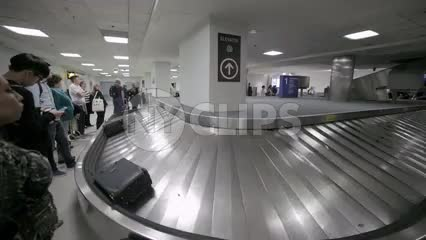 suitcases on conveyor belt at LaGuardia Airport baggage claim