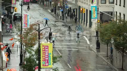 people walking with umbrellas on rainy day - raining on 8th street NYC