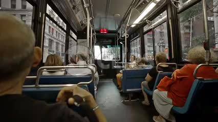 interior MTA bus riding in Manhattan - passengers speaking spanish on summer day in NYC