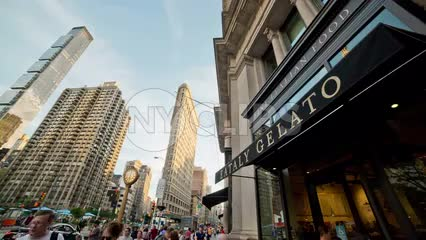 Eataly Gelato restaurant in Flatiron District with skyscraper and 5th ave clock on summer day in NYC