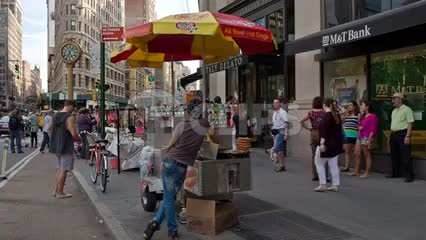 hot dog vendor on summer day in Flatiron District with 5th Ave clock on sunny day in Manhattan NYC
