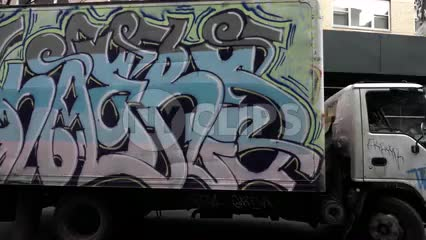 beautiful graffiti truck spray-painted with colorful art driving away in morning in NYC