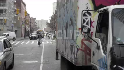 man on bicycle riding past gritty graffiti truck in morning in NYC