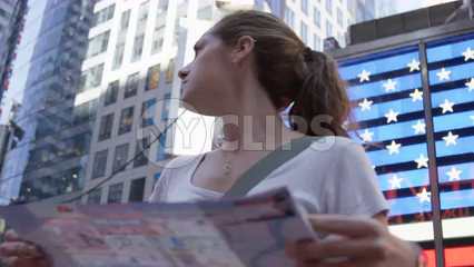 close-up of attractive female tourist looking at map in front of Times Square American flag LED - slow motion 4K in New York City