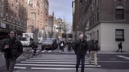 people walking down Lower 5th Ave in fall or winter cold day Empire State Building in distance at crosswalk in Manhattan slow motion